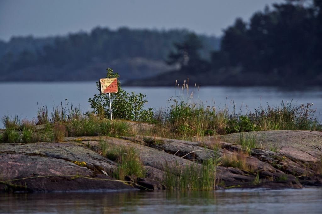 Den gulröda skylten betyder att det är förbjudet att landstiga och vistas i vattenområdet 100 ut från stranden